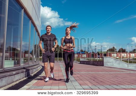 Young Athletic Couple Man Woman Running Summer City Background Building And Clouds, Sportswear. Trai