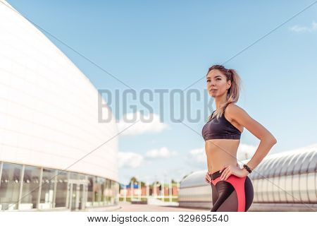 Young And Athletic Woman Standing In City On Summer, Background Building, Sportswear. Athletics Trai