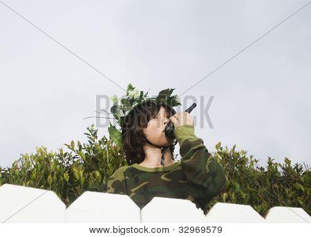 Mixed Race boy talking on walkie talkie