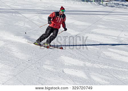 Pyrenees, Andorra - February 13, 2019: A Skier Descends From The Mountain At High Speed At A Ski Res