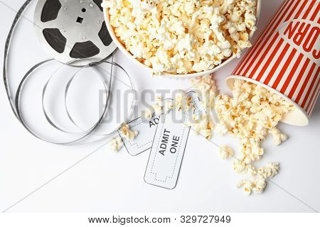 Popcorn, Tickets And Movie Reel On White Background, Top View. Cinema Snack