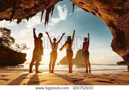 Four Happy Friends Are Celebrating Something On Beach And Standing In Small Cave Against Sunset Sea