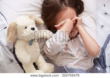 Sleepy Pretty Little Child Rubbing Her Eyes In Morning While Lying In Bed. Lovely Small Child With D