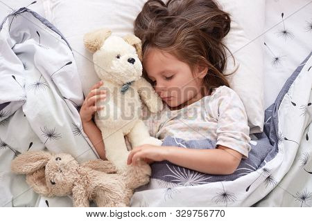 Close Up Portrait Of Beautiful Cute Little Girl Sleeping Peacefully And Hugging Her Stuffed Toys In