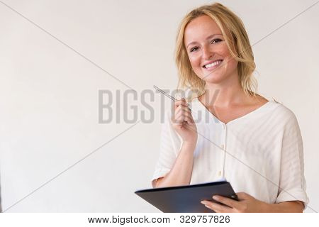 Happy Cheerful Young Woman Filling Up Form, Holding Pen And Folder. Beautiful Blonde Woman In Casual