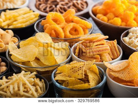 All Classic Potato Snacks With Peanuts, Popcorn And Onion Rings And Salted Pretzels In Bowl Plates O