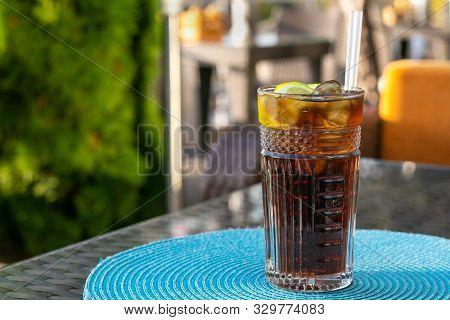 Alcohol Cocktail - Long Island Iced Tea. Iced Tea With Lemon In A Glass. Brown Ice Drink On Table An