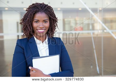 Happy Friendly Legal Expert Posing Outside. Young Black Business Woman Standing At Glass Wall, Holdi