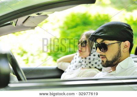 Young couple enjoying in car at fast pace