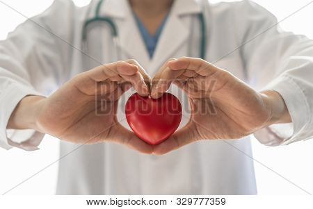 Cardiovascular Disease Doctor Or Cardiologist Holding Red Heart In Clinic Or Hospital Exam Room Offi