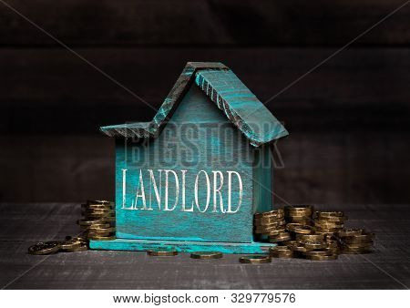 Wooden House Model With Coins Next To It With Conceptual Text. Landlord
