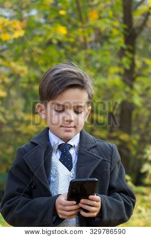 Kids And Gadgets Concept. A Smiling Happy Schoolboy Is Standing In The Street In A Beautiful Busines