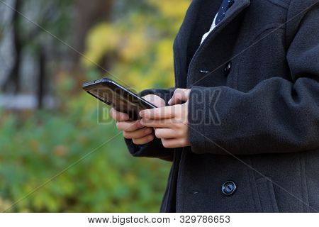 A View Of The Hands Of A Little School-age Boy Holding A Smartphone And Typing A Message, Browsing T
