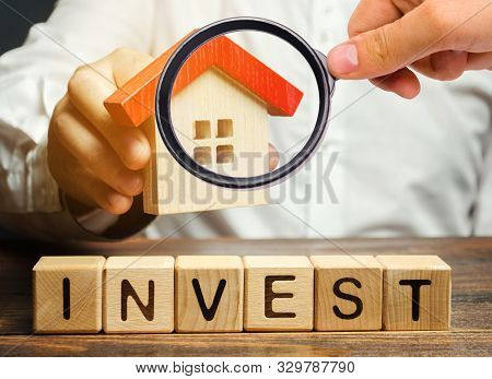 Wooden Blocks With The Word Invest And House In The Hands Of A Businessman. The Concept Of Investing