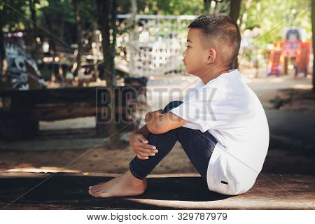 Asian Kid Lonely Boy Sitting In Feel Solitary Sad Mood At The Park Playground For Children