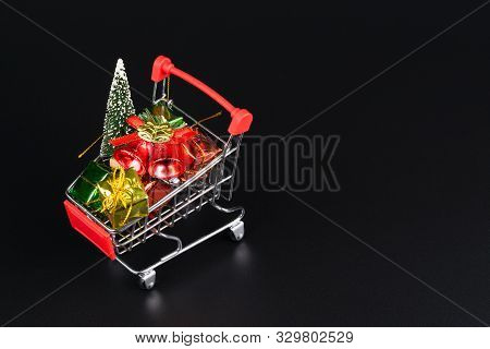 Shopping Cart With Christmas Tree And Miniature Gift Boxes On Black Background. Christmas And New Ye