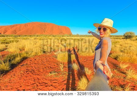Uluru, Northern Territory, Australia - Aug 23, 2019:follow Me, Smiling Girl With Hat Holding Hands A