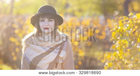 A Pretty Woman Of 30-35 Years Old With A Beautiful Smile In A Hat And Coat Near A Yellow Bush, Autum