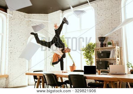 Young Caucasian Businessman Having Fun Dancing Break Dance In The Modern Office At Work Time With Ga