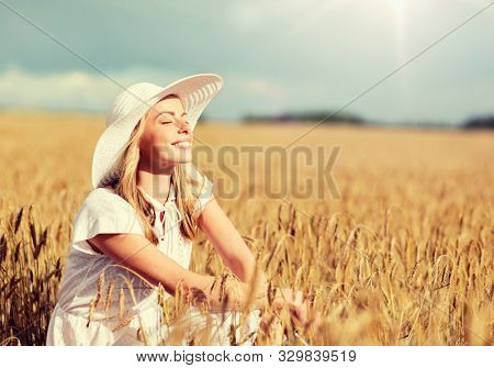nature, summer holidays, vacation and people concept - happy young woman in white dress and sun hat enjoying sun on cereal field
