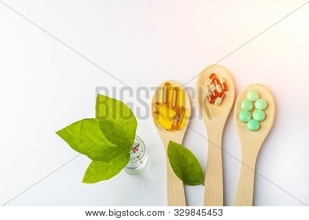 Herbal Capsule, Natural Vitamins, Mineral Supplement At Wooden Spoon On A White Background. Concept