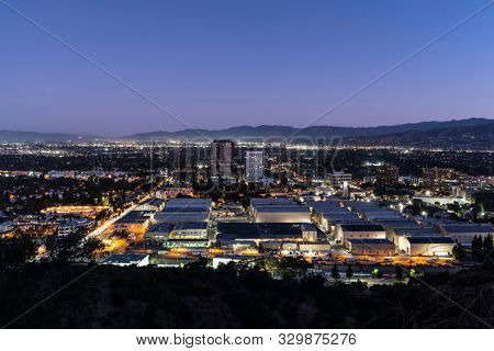 Burbank, California, USA - October 25, 2019:  Twilight predawn morning view of historic Warner Bros studio sound stages and Burbank Media District buildings in the San Fernando Valley.
