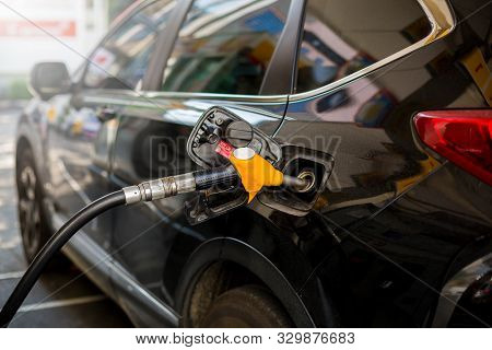 Hand Refilling The Black Car With Fuel At The Gas Station. Oil And Gas Energy. Black Car In Gas Stat
