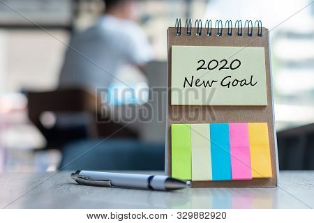 2020 New Goal Word On Note Paper With Pen On Wooden Table. Resolution, Strategy, Solution, Goal, Bus