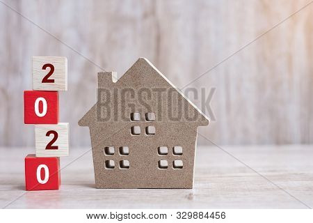 2020 Happy New Year With House Model On Wooden Background. Banking, Real Estate, Investment, Financi