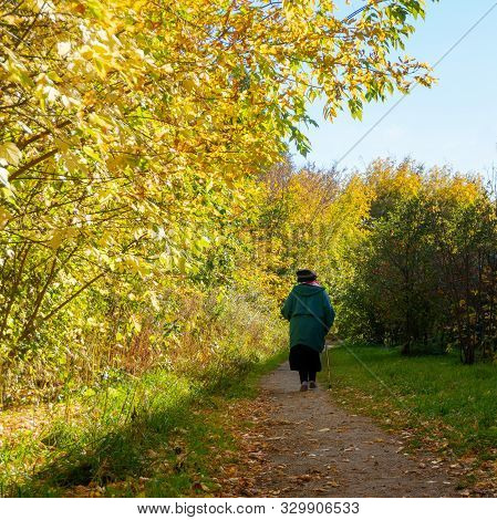 An Elderly Lonely Woman With A Cane Walking In An Autumn Park. The Concept Of The Need To Help Elder