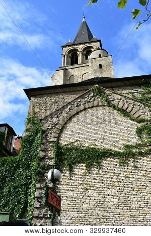 Church of Saint Germain des Pres. Bell tower with stone wall, ivy and Metro sign from the Boulevard Saint Germain. Paris, France.
