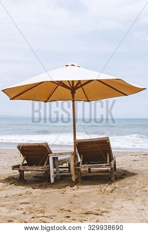 Single Umbrella With Two Beach Chairs On Empty Beach.