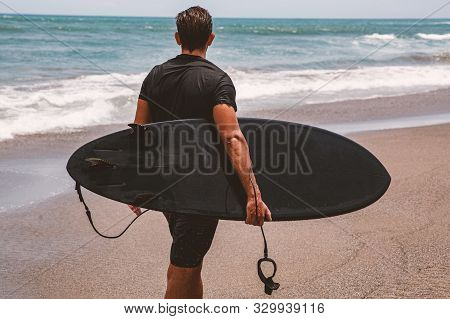 Surfer In A Black Wetsuit Is Ready To Enter The Water.