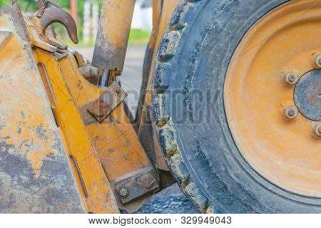 Scratched Metal Bucket Of A Small Old Orange Tractor. Old Tractor Wheel. Road Construction, Repair C