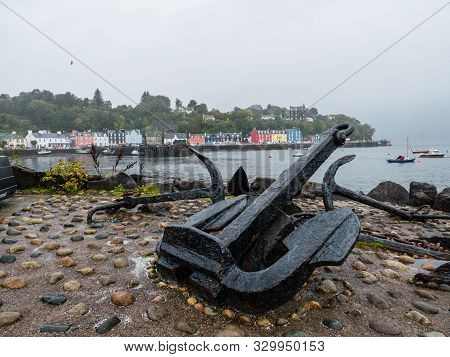 Old Anchor With View Of Scottish Tobermory Town In The Background