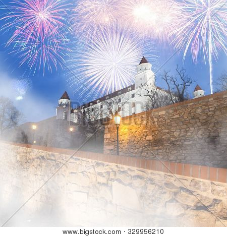 Twilight View Of Lit Bratislava Castle  With Dramatic Sunset Cloudy Skyline And Firework Parade Duri