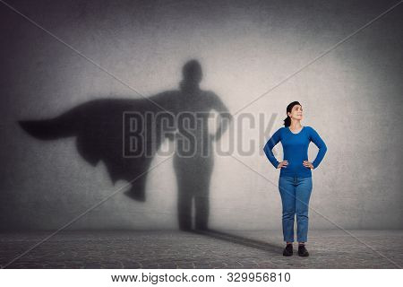 poster of Brave woman keeps arms on hips, smiling confident, casting a superhero with cape shadow on the wall. Ambition and business success concept. Leadership hero power, motivation and inner strength symbol.