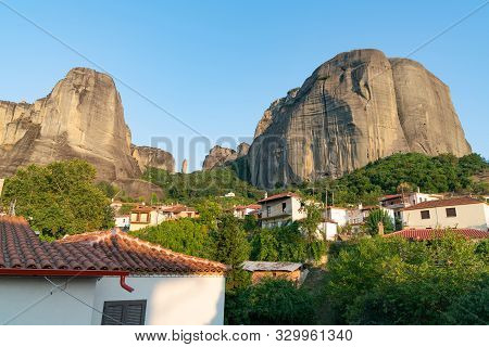 Houses And Church In Foothills Among Trees In Valley Below Towering Converging Rocks And Pinnacles A