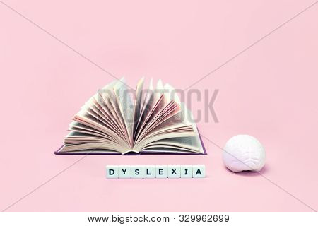 Dyslexia Word With A Brain Stress Relief And Open Book On Pink Background, Reading Difficulty And Di
