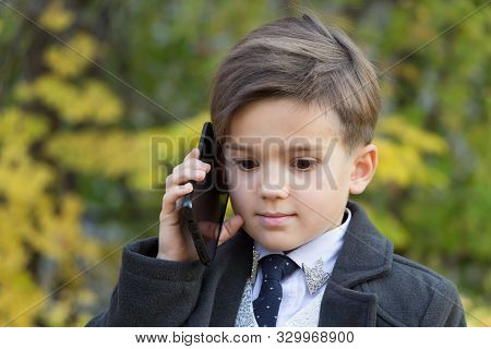 Portrait Of Smiling Little Young Businessman Talking By Phone On Autumn Background. Little Adults. T