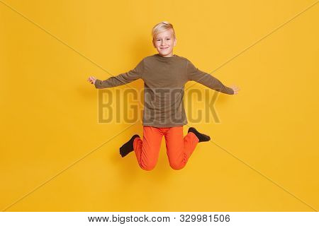 Flying Young Boy Jumping With Spreading Arms Raised. Full Length Studio Shotof Male Kid With Pleasan