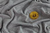 Golden bitcoin shiner on gray crumpled cotton cloth poster