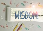 Text sign showing Wisdom. Conceptual photo quality having experience knowledge and good judgement something Stationary and torn cardboard placed above a wooden classic table backdrop. poster