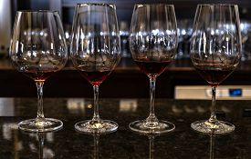 Four Crystal Glasses Filled With Red Wine In A Winery Tasting Room