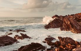 Coastal Cliffs By The Ocean With Waves. Sunset.