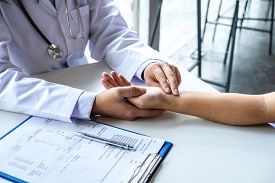 Doctor Checking Measuring Pressure On Patient's Hand Pulse By Hands, Medical And Healthcare Concept