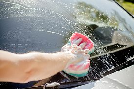 Male Hand With Tool For Washing Windows, Car Wash.man Washing A Soapy Blue Car With Colorful Sponge.