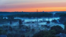 Misty Sunrise At Suburbs With High Voltage Power Lines Going Through It. Suburbs In The Forest. Fog