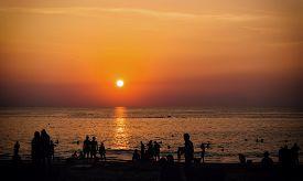 Silhouettes Of People Over Sea Background At Sunset. Thailand, Phuket, Karon Beach