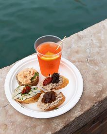 Traditional Venetian Food And Drink Cicchetti And Aperol Spritz With Turquoise Green Water Of Canal.